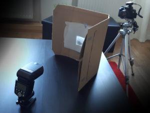Der Blitz leuchtet auf das Transparentpapier von unserem Negativhalter. Das Negativ wird dadurch von hinten beleuchtet, wie bei einem Leuchttisch. Von vorne fotografiert die Kamera das Negativ.